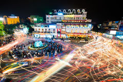 People and vehicles light trails crowd on busy intersection loca Stock Images
