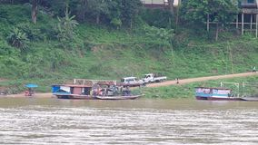 People and vehicles are moving out from the local ferry boat. Luang prabang, Laos - AUGUST 8, 2015: people and vehicles are moving out from the local ferry boat stock video footage