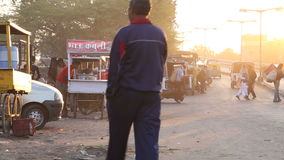 People and vehicles at sunset at street in Jodhpur. JODHPUR, INDIA - 12 FEBRUARY 2015: People and vehicles at sunset at street in Jodhpur stock video footage