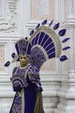 Person wearing a Venice mask and a purple and gold costume at the Venice Carnival in Venice Italy royalty free stock photography