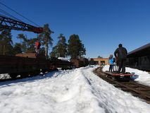People, a view from the back, riding on a hand trolley, winter, narrow-gauge railway in the forest with pine and spruce, clear day stock photography