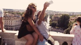 People view the Italian city landscape from the observing platform above the Piazza del Popolo. A happy couple of. Tourists is making a selfie. Tourists take stock video