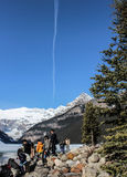 People  viewing Lake Louise and mountains with jet contrail Royalty Free Stock Image