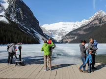 People  viewing Lake Louise and mountains with jet contrail Royalty Free Stock Photos