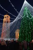 People at Vilnius Christmas market and Xmas tree with garlands Stock Photography
