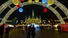 People visit Christmas market near town hall at evening stock video footage
