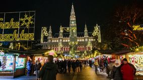 People visit Christmas market near town hall at evening stock footage