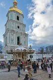 Saint Sophia Cathedral in Kiev, Ukraine. Christmas time. People visit Christmas vintage carousel in front of Saint Sophia Cathedral bell tower. Saint Sophia Royalty Free Stock Images