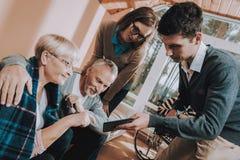 People Visit Older. Grandchildren Hold Laptop. stock photos