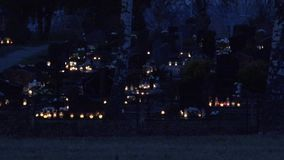 People visit tombs of dead family members in rural graveyard at night. 4K. People visit tombs of dead loved ones in rural graveyard at night. Day of Dead. Focus stock video footage