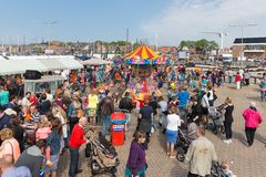 People visiting a fare at a national Dutch holiday. URK, THE NETHERLANDS - APR 26: Unknown people visiting a fare at a national holiday at the harbor of Urk on Royalty Free Stock Image