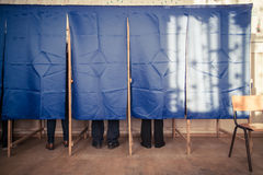 People vote in voting booth. People vote in a voting booth at a polling station royalty free stock photo