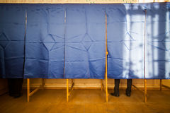 People vote in voting booth. People vote in a voting booth at a polling station royalty free stock image
