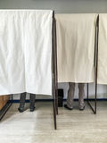 People voting in polling booths at a voting station. Legs of people voting in polling booths at a voting station Stock Photo
