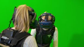 People in VR helmets communicate and laugh. Guys in camouflage play game in virtual reality on a green background.