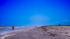 Low Tide Stroll Along The Beach. People wade in the surf at the beach in the morning stock image