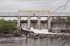 People wade in water by huge Chute Pond dam Royalty Free Stock Photo