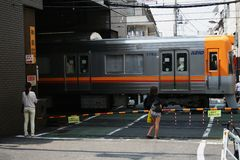 People wait as commuter train passes through street level crossing in central Tokyo. Stock Photo