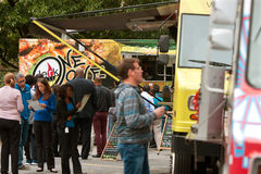 People Wait In Line To Buy Meals From Food Trucks Stock Photos