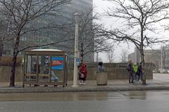 People wait for a public bus in wet chilly weather in downtown Cleveland, Ohio, USA. People wait at an RTA bus stop on East 9th Street in downtown Cleveland stock photo