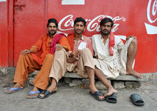 People wait at station, trains delayed. Three poor friends waiting at Karachi railway station, delay in trains has become a common practice here Stock Images