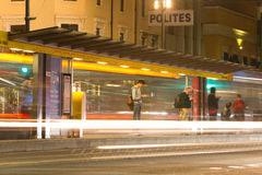 People waiting for the Adelaide tram at night. Adelaide, Australia - June 22, 2016: Individuals wait for a tram in King William Street, Adelaide at night. The Stock Photo