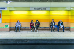 People waiting at a bench in the subway station hauptwache. FRANKFURT, GERMANY - OCT 3, 2015: people waiting at a bench in the subway station hauptwache Stock Photos