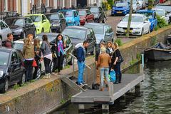 People waiting a boat near the river canal (Nieuwe Gracht). Haarlem, the Netherlands - June 20, 2015: People waiting a boat near the river canal (Nieuwe Gracht Stock Images