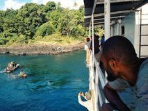 People waiting on a cargo boat next to a stunning tropical island while it uploads with a local outrigger canoe. Olal village, Ambrym Island / Vanuatu - 9 JUL royalty free stock photos