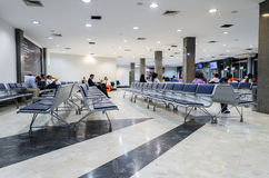 People waiting for departure and some empty chairs on departure Royalty Free Stock Photos
