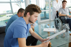 People waiting for doctor at hospital Stock Photography