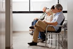 People Waiting For Doctor In Hospital Lobby. Row of multiethnic people sitting side by side while waiting for doctor in hospital lobby Royalty Free Stock Photos