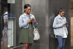 People are waiting for friends near Covent Garden, buried in mobile phones Royalty Free Stock Photography