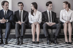 People waiting for job interview. Business people waiting for job interview sitting in a row Stock Photo