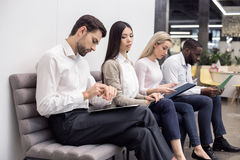 People Waiting for Job Interview Concept. Time for job interview. Young men and women in office. They sitting, holding CVs and waiting for job interview. One men Royalty Free Stock Photos