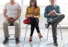 People waiting for job interview. Group of people waiting for job interview and using mobile phone Royalty Free Stock Images