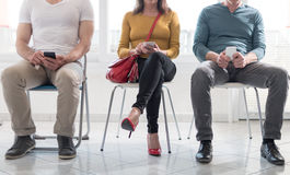 People waiting for job interview. Group of people waiting for job interview and using mobile phone Stock Photo