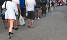 People waiting in line. Feet of people in casual clothes waiting patiently in line Stock Photo