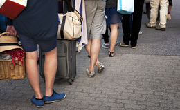 People waiting in line. Feet of people with luggage in casual clothes waiting patiently in line royalty free stock photos