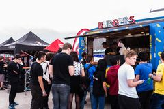 People waiting in line to buy burgers from a food truck Stock Image