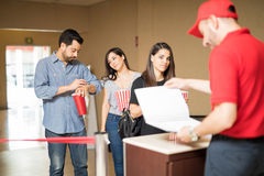 People waiting in line to see a movie. Line of annoyed people waiting to see a movie while an employee at the cinema theater looks at some list Royalty Free Stock Photo