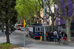 People waiting near a blue historic tram. Barcelona Spain - April 14. 2012: People waiting near a blue historic tram Royalty Free Stock Image