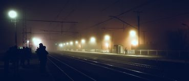 People are waiting for a passenger train at the station on a dark night. stock image
