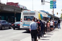 People waiting in queue on the public bus station to get on the bus in Montreal, Quebec, Canada stock image