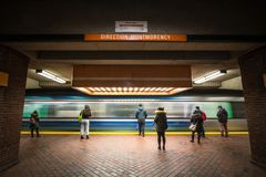 People waiting for a subway in Snowdon station platform, orange line, while a metro train is coming, with a speed blur. MONTREAL, CANADA - NOVEMBER 3, 2018 stock images