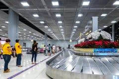 009 - People Waiting Suitcase on luggage conveyor belt at baggage claim at Suvarnabhumi Airport Bangkok. stock photography