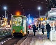 People by a waiting tram. People walking close by a waiting tram with number 15 on the Kaponiera stop by night on circa January 2018 in Poznan, Poland Stock Photo