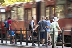 People waiting for a tram on a sunny day. Belgrade, Serbia - June 1, 2018 : People standing at a bus stop and waiting for public transportation on a sunny spring Stock Photos
