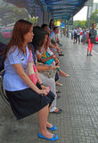 People are waiting for transport at bus stop Stock Image