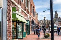 People waking on a Brick Pavement Lined with Shops and Restaurants in New Haven, CT. New Haven, CT, USA - October 20, 2016: People Walking on the brick sidewalk royalty free stock photos
